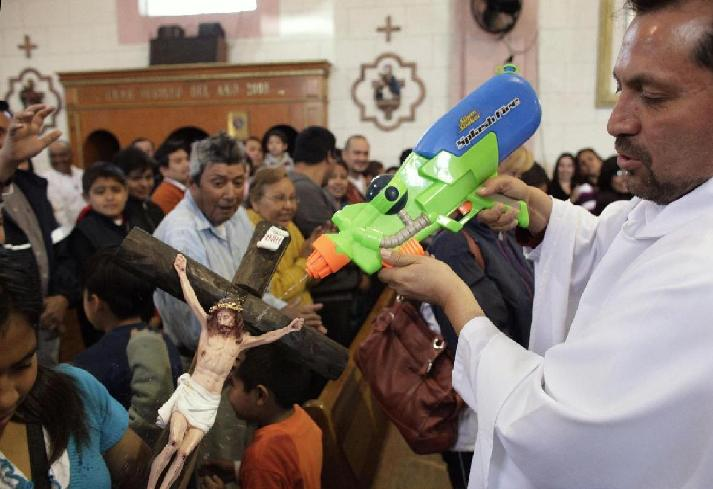 Catholic priest Alvarez sprays holy water from a water gun to bless a crucifix during mass at the Ojo de Agua church in Saltillo